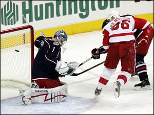 The Red Wings' Tomas Holmstrom slips the puck past Blue Jackets goalie Steve Mason in the first period. Detroit got the game-winning goal from Johan Franzen with 46.6 seconds left.