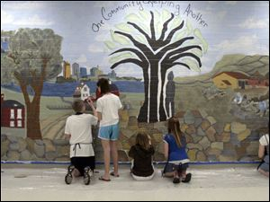 Volunteers paint scenes from here and from Lesotho, Africa, on a community mural that fits the length of a cafeteria wall.