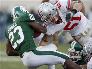 Ohio State defender Ross Homan hits Michigan State running back Javon Ringer (23). Without James Laurinaitis and Marcus Freeman, Homan should play a bigger role for the Buckeyes.