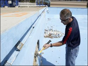 Neal Graf, Wauseon Parks and Recreation director, chips away at the side of the Reighard Park pool. Contractors  estimates for concrete patching and repainting started at $67,000, and that didn t cover plumbing repairs the pool also needed, Mr. Graf said.