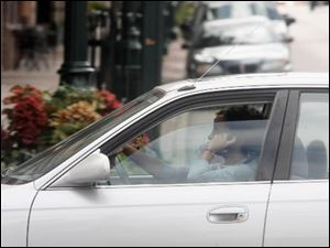 A motorist talks on a hand-held cell phone as she travels on East Wooster Street near Main Street in Bowling Green. Voters are being asked to outlaw such behavior.
