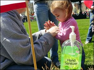 Amanda Scraker, left, sanitizes the hands of her daughter, Sydney, 2, before letting her play at a petting zoo in Holland, Mich. Ms. Scraker is concerned about swine flu.