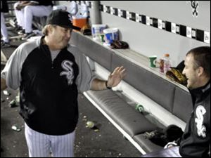 White Sox pitching coach Don Cooper, left, talks with his ace, Mark Buehrle, in the dugout after Buehrle took a perfect baseball game into the seventh inning against the Tigers.