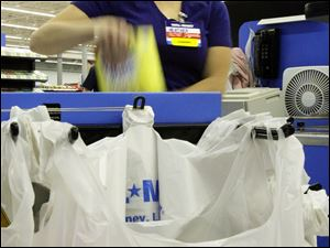 Wal-Mart cashier Heather Martin bags purchases in Los Angeles yesterday.