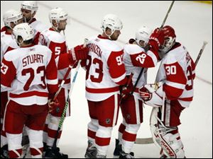Detroit Red Wings goalie Chris Osgood receives congratultions from his teammates at the end of Game 4.