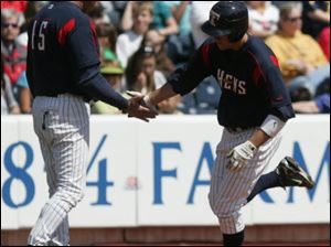 Mud Hens manager Larry Parrish congratulates outfielder Jeff Frazier on his two-run homer in the fourth inning.