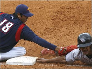 Mud Hens pitcher Fu-Te Ni tags out Lehigh Valley s Jason Ellison at fi rst base in the eighth inning. Ni threw to first for a pickoff, then made the tag in a rundown.