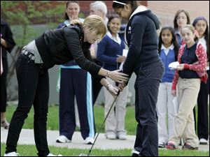 CTY farr12p 05/11/09  The Blade/Dave Zapotosky Caption: Professional golfer Paula Creamer, defending champion of the  Jamie Farr Owens Corning Classic,  shows Alexia Franco, 13, a student at Queen of Apostles School in Toledo, Ohio, how to hold a golf club during a visit to the school, Monday, May 11, 2009.