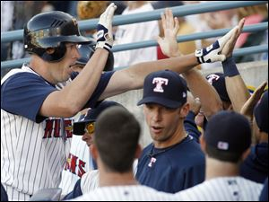 Toledo's Mike Hessman, left, high-fives teammates after he belted a two-run homer last night at Fifth Third Field.