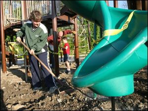 Carol Kutcher rakes the ground before mulch is put on the new playground at OLPH.