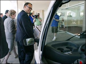 Ed Montgomery, the federal director of recovery for auto communities and workers, surveys a hybrid car during his visit.
