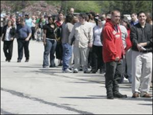 Area unemployed workers stand in line at the Toledo Job Fair earlier this month.