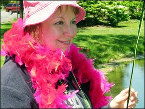 Pam Ackley Flowers of West Liberty, Ohio, wears a pink boa, an honor accorded Reeling and Healing participants for catching their first trout on a flyrod. Patti Schebil of LaSalle, Mich., takes a good look at her first trout taken on a flyrod.