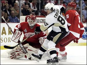 Nicklas Lidstrom, right, battles with the Penguins' Sidney Crosby in front of goalie Chris Osgood.