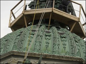 The statue of Lady Justice is hauled to the top of the courthouse dome, where workers from Midstate Construction wait to secure it in place. It has held its lofty perch atop the stately clock tower since 1899.