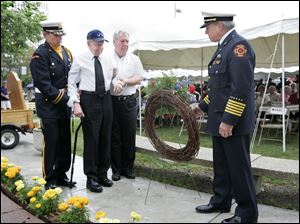 Toledo Fire Chief Michael Wolever waits with a wreath to be placed at the Firefighters Memorial in Chub DeWolfe Park by retired Deputy Chief Richard Hunt, assisted by his son Robert and fire Lt. Richard Knight, left. The elder Mr. Hunt, 92, is the department s second-oldest retiree. Yesterday s ceremony, marking the 48th anniversary of the Anthony Wayne Trail fire, was preceded by an awards ceremony.