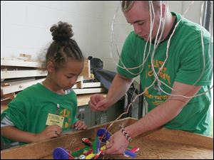 Clay High School alumnus Derek Partin assists Daijah Sartor, 8, with her car during the Robot Wars program.