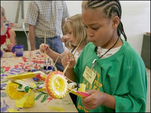 Rebekah Koster, 7, left, and Gabriel Dudley, 11, paint robotic cars at Clay High School. The youths were among 21 children aged 7 to 12 to participate in the school s robot wars program.
