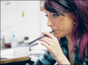Sara Jacobs smokes an InLife electronic cigarette in her office during work.