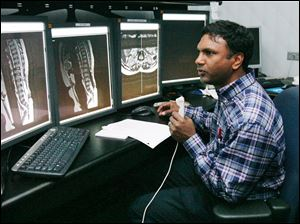 Dr. Ramesh Avna records his findings from a group of images at St. Vincent Mercy Medical Center. The hospital dropped its longtime local radiology provider for a California company.