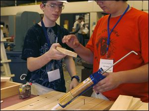 Clarence McCune, 14, left, and Ben Diehl, also 14, glue a cross-piece for the chair they are making at the camp.