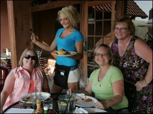 Terry Helbing, waitress Alyssa Morelock, Karen Johansen and Rosanne Babiuch, on the patio at Tangos Mexican Cantina patio in Toledo. They are life-long friends who meet about once a month for dinner.
