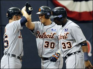 Magglio Ordonez, center, is met by Ryan Raburn, left, and Marcus Thames after his three-run home run, but it wasn't enough.