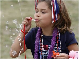 Dressed to celebrate, Alexis Hugo, 7, of Detroit blows bubbles at Promenade Park.