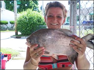 Nicole Jiminez shows off the 18 -inch, 4-pound pacu she took from Maumee Bay off Edgewater Drive in Point Place.