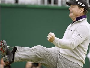 Tom Watson celebrates as he rolls in a 45-foot putt on the 18th green to take a share of the lead.