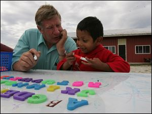 Ken Green works on language fundamentals with Gustavo Ramirez, 3, at a migrant camp in Woodville, Ohio. The boy is part of the Woodmore district's summer education program for migrants.