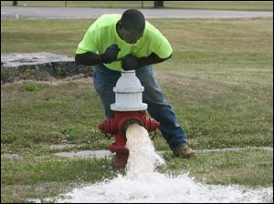 Inspector Robert Townsend checks a hydrant at the corner of Woodruff Avenue and Warren Street for water flow.