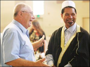 Larry Short, left, of Wauseon, shares a laugh with Imam Salie.