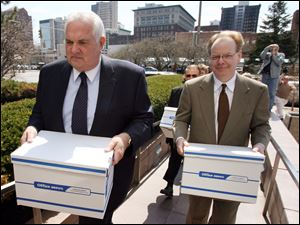 Tom Schlachter, left, and Andy Stuart of Take Back Toledo carry boxes with about 40,000 signatures to recall mayor Carty Finkbeiner into Government Center in April.