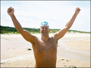 John Muenzer celebrates crossing the English Channel after he reached his destination in France. Muenzer set six schoolrecords when he was a swimmer at the University of Toledo.