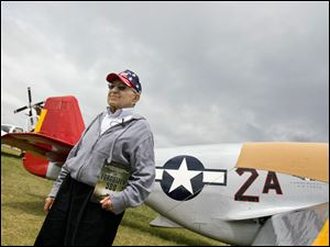 Art Jibilian of Fremont stands next to a P51 Mustang, the aircraft flown by the Tuskegee Airmen during World War II. Mr. Jibilian and the airmen were honored at AirVenture 2009 in Oshkosh, Wis.