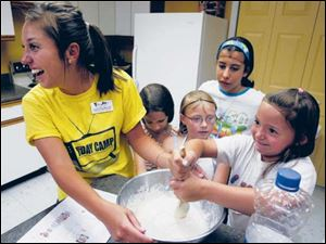 Laura Rodriguez, left, assistant director, helps Madelyn Jeffrey,7, Ally Devries, Ashley Moylan, 13, and Gabrielle Whitzel, 6, mix pancake batter.