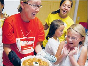 Ally Devries, 8, is excited when Culinary Camp instructor Amy Tanner takes the monkey bread the campers made from the oven.