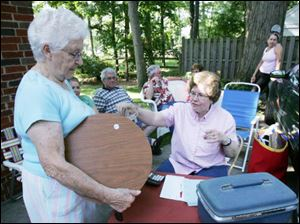 Margaret Trowbridge, left, pays Judy Dilworth for an item at Mrs. Dilworth's sale.