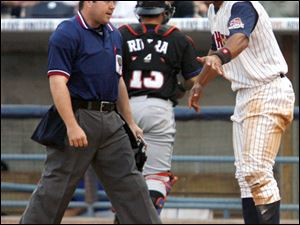 Wilkin Ramirez, right, argues with the home plate umpire after being called out in the third.
