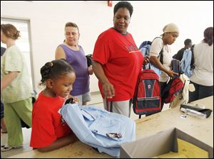 Slug: REL BACKPACKS20p          Date 8/20/2009           The Blade/ Amy E. Voigt           Location: Toledo, Ohio  CAPTION:  Kennedy Gibson-Harrison, left, reacts to her new backpack and school supplies while her mother Shelly Taylor (cq), rightfrom Toledo, ushers her through the line at The Salvation Army on August 20, 2009.