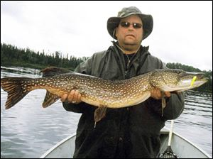 Terry Francis of Monclova proudly shows off a 41-inch northern pike he landed during a trip to Ontario.