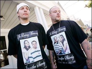 Brothers Gerald, left, and Raymond Smith, don T-shirts in memory of their slain sister, Jennifer Shively, during yesterday's news conference at the home of Esther Swope, the victim's mother.