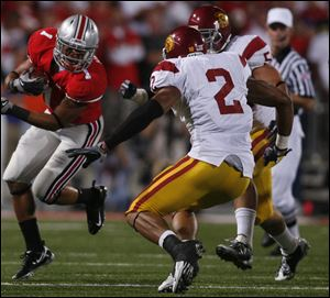 Ohio State's Dan Herron tries to get past USC's C.J. Gable in Saturday night's game in Columbus.