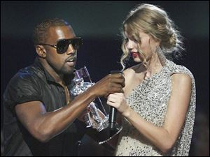 "Singer Kanye West takes the microphone from singer Taylor Swift as she accepts the ""Best Female Video"" award during the MTV Video Music Awards on Sunday, Sept. 13, 2009 in New York."