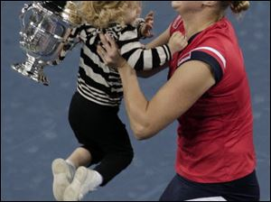 Kim Clijsters of Belgium lifts her daughter Jada after winning the women's championship over Caroline Wozniacki, of Denmark, at the U.S. Open tennis tournament in New York, Sunday, Sept. 13, 2009.