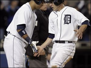 Carlos Guillen, left, greets Brandon Inge after Inge scored on a two-run single by Ramon Santiago in the second inning. The Tigers can clinch the AL Central Division with a victory today.