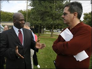 Toledo mayoral candidate Mike Bell, left, talks to city resident Cliff Warstler outside the Toledo Fire Fighters Federal Credit Union near Fire Station 23 on West Laskey Road yesterday.