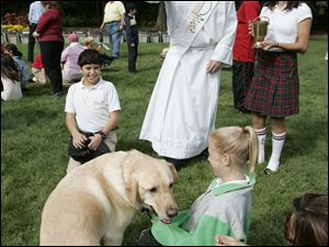 Deacon Tom Sheehan blesses Newman, held by owner Helen Waldie, 10, a student at Sylvania