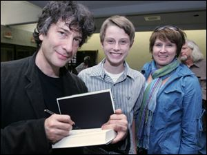 Author Neil Gaiman signs one of his books for Derek Kastner and his mom, Kim Kastner, of Sylvania. The author said the words, So what happened next? made him finish 'The Graveyard Book.'